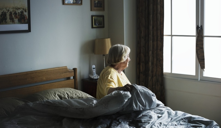 Older woman getting out of bed