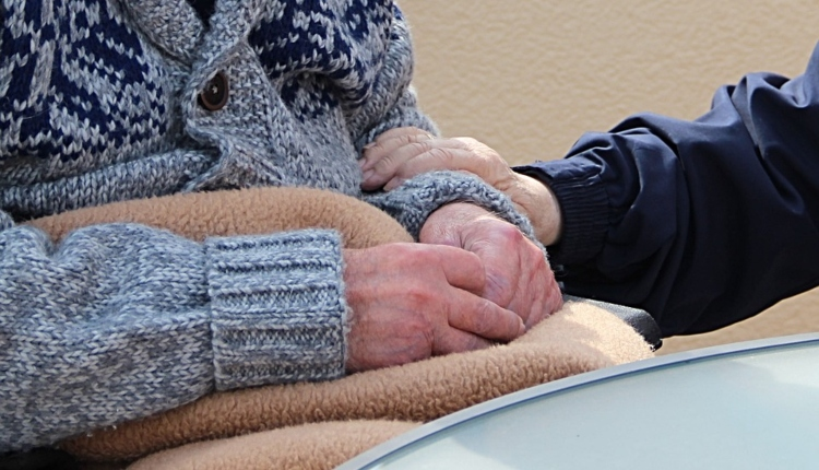 Older person's hands with another person's hand on their arm